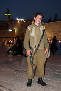 An IDF soldier stands at the Western Wall Plaza in the Old City of Jerusalem. She had been working security during an air force graduation ceremony that just finished.