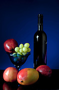 Apple still life in blue with mango, grapes and a bottle of red wine