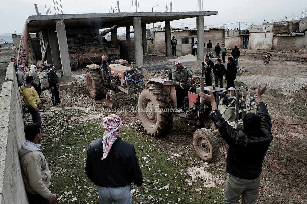 SYRIA - Homs province: Rebels try to start the motor of a tank whose crew defected from government forces in Homs province on February 22, 2012. ALESSIO ROMENZI
