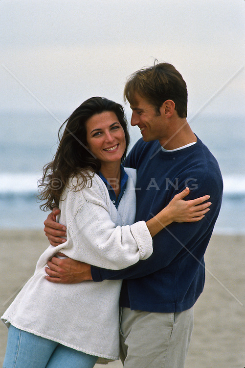 Couple being playful and romantic on the beach in Santa Monica, CA