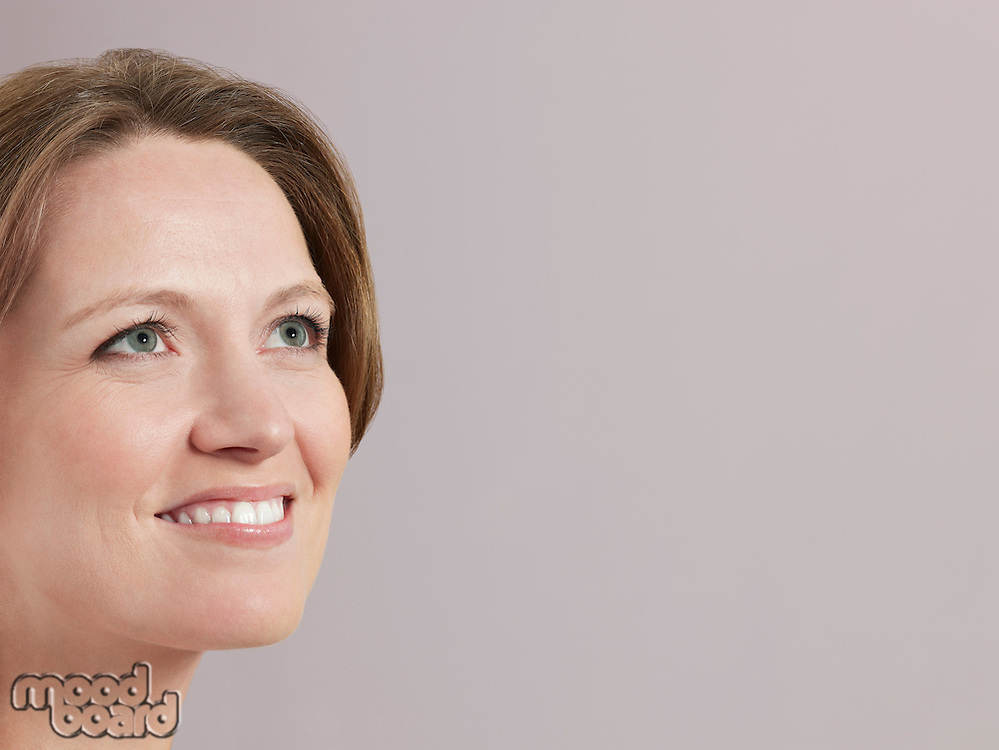 Mid-adult woman looking up and smiling close-up