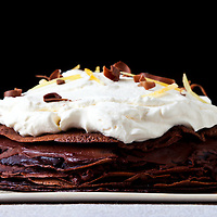 A dessert created with layers of chocolate crepes and topped with whipped cream and chocolate shavings.