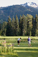 Teenage boy tees off at Nicklaus North in Whistler, BC Canada.