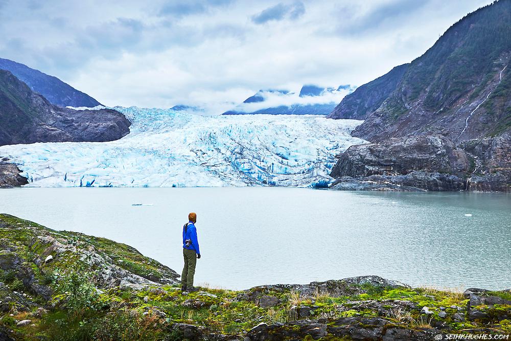 A hiker admires the view of Mendenhall Glacier across the lake near Juneau, Alaska.