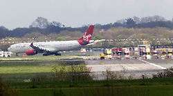 © Licensed to London News Pictures. 16/04/2012, London, UK.  A Virgin Atlantic plane is being moved away from the runway at London Gatwick Airport after forced to make an emergency landing after smoke was reported in the cabin. Monday, April 16, 2012. The Virgin Atlantic VS27 was bound for Orlando in the US from Gatwick Airport. Photo credit : Sang Tan/LNP
