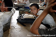 A student without classroom materials sits at his learning table at The Ban Buamlao Primary School in Ban Buamlao, Laos.