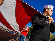 """11 NOVEMBER 2013 - PHOENIX, AZ: A US Navy sailor helps carry an American flag at the Phoenix Veterans Day parade. The Phoenix Veterans Day Parade is one of the largest in the United States. Thousands of people line the 3.5 mile parade route and more than 85 units participate in the parade. The theme of this year's parade is """"saluting America's veterans.""""    PHOTO BY JACK KURTZ"""