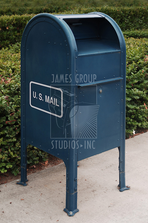 blue US mailbox on sidewalk
