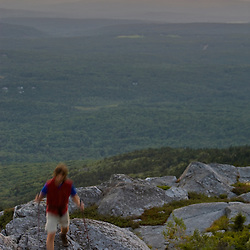 A hiker at sunset near the summit of Mount Monadnock in New Hampshire's Monadnock State Park.