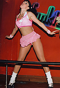 A female dancer dressed in a skimpy outfit with fishnet tights at Funktup, December 2004