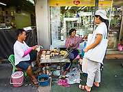 29 NOVEMBER 2015 - BANGKOK, THAILAND:  Food vendors sell grilled bananas on their last day in the Amulet Market on Maharat Road in Bangkok.  Hundreds of vendors used to sell amulets and Buddhist religious paraphernalia to people in the Amulet Market, a popular tourist attraction along Maharat Road north of the Grand Palace near Wat Maharat in Bangkok. Bangkok municipal officials announced that they are closing the market and forcing vendors to relocate to an area about one hour outside of Bangkok. The closing of the amulet market is the latest in a series of municipal efforts to close and evict street vendors and markets from areas that have potential for redevelopment. The street vendors were evicted from the area on Sunday, Nov. 29.      PHOTO BY JACK KURTZ