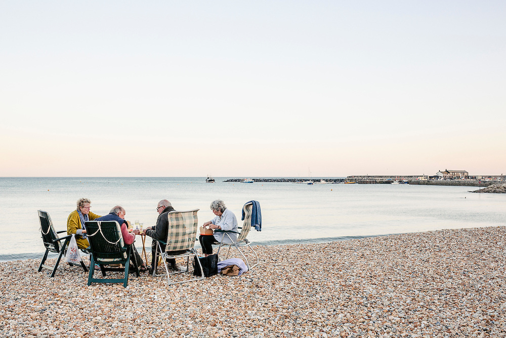 Old age pensioners enjoying a picnic by the sea near the Cobb.