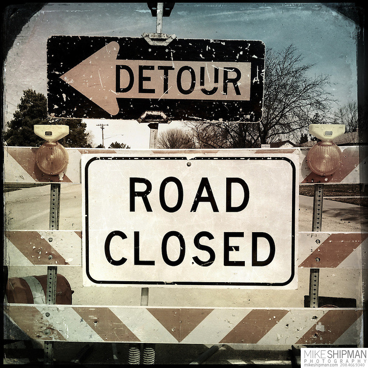 Road closed and detour signs on a residential street