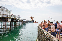 © Licensed to London News Pictures. 09/08/2020. Brighton, UK. Kids can be seen jumping of the pontoon alongside the Brighton Palace Pier in to the sea in Brighton And Hove on the hottest weekend of the year so far with temperatures going well in the 30C's in the South Coast. Photo credit: Hugo Michiels/LNP