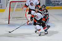 KELOWNA, CANADA, OCTOBER 11: Dylan Busenius #2 of the Medicine Hat Tigers is checked by Carter Rigby #11 of the Kelowna Rockets as the Medicine Hat Tigers visited the Kelowna Rockets on October 11, 2011 at Prospera Place in Kelowna, British Columbia, Canada (Photo by Marissa Baecker/shootthebreeze.ca) *** Local Caption ***Dylan Busenius;Carter Rigby;