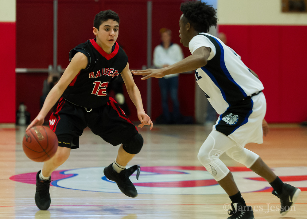 Watertown High School freshman Gabe Spinelli dribbles past Jeremiah E. Burke High School i junior Devante Jamison during the MIAA Division 3 state semifinal game in Burlington, March 14, 2018. The Raiders won the game, 66-61. [Wicked Local Photo/James Jesson]