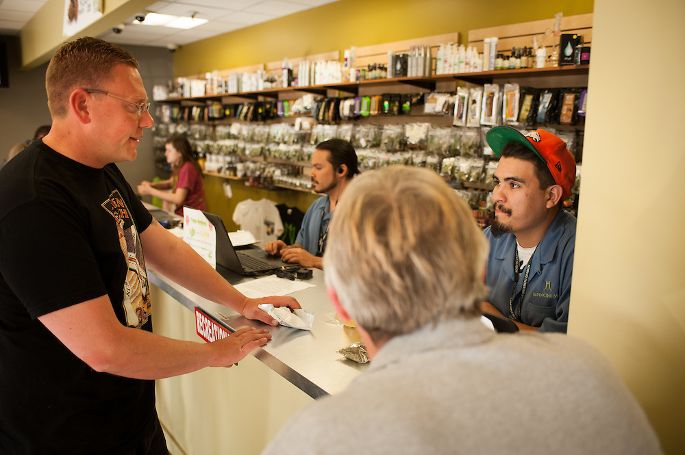 Armando Rios, a budtender, helping customers at the recreational sale counter at Medicine Man.
