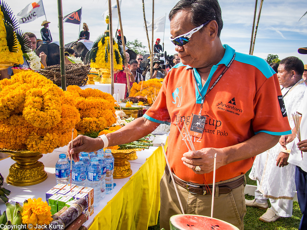 "29 AUGUST 2013 - HUA HIN, PRACHUAP KHIRI KHAN, THAILAND: A man participates in an elephant blessing before the King's Cup Elephant Polo Tournament in Hua Hin. The tournament's primary sponsor in Anantara Resorts and the tournament is hosted by Anantara Hua Hin. This is the 12th year for the King's Cup Elephant Polo Tournament. The sport of elephant polo started in Nepal in 1982. Proceeds from the King's Cup tournament goes to help rehabilitate elephants rescued from abuse. Each team has three players and three elephants. Matches take place on a pitch (field) 80 meters by 48 meters using standard polo balls. The game is divided into two 7 minute ""chukkas"" or halves. There are 16 teams in this year's tournament, including one team of transgendered ""ladyboys.""    PHOTO BY JACK KURTZ"