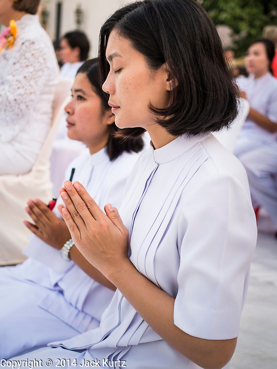 23 NOVEMBER 2014 - BANGKOK, THAILAND: Women pray at a mass alms giving ceremony in Bangkok Sunday. 10,000 Buddhist monks participated in the ceremony on Rajadamri Road in front of Central World shopping mall. The alms giving was to assist Buddhist temples in the insurgency wracked southern provinces of Thailand, where Buddhist monks on their alms rounds have been targeted by Muslim extremists. The ceremony was sponsored by Wat Phra Dhammakaya, the center of the Dhammakaya Movement, a Buddhist sect founded in the 1970s. The temple has become active in Thai politics.    PHOTO BY JACK KURTZ