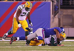 Dec 4, 2011; East Rutherford, NJ, USA; Green Bay Packers quarterback Aaron Rodgers (12) is sacked by New York Giants defensive end Justin Tuck (91) during the first half at MetLife Stadium.