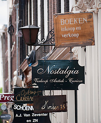 Many shop signs above traditional shops in Grachtengordel district of Amsterdam Netherlands