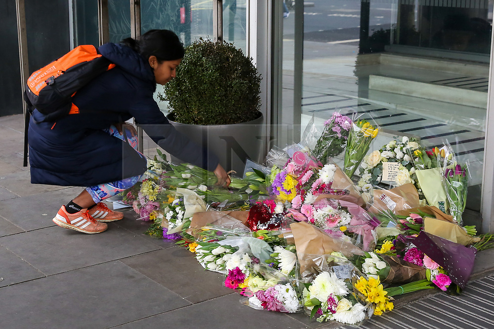 © Licensed to London News Pictures. 16/03/2019. London, UK. A woman places flowers at High Commission of New Zealand in London. A gunman killed 49 worshippers at the Al Noor Masjid and Linwood Masjid mosques in Christchurch, New Zealand on 15 March. The 28-year-old Australian suspect, Brenton Tarrant, appeared in court on 16 March and was charged with murder. Photo credit: Dinendra Haria/LNP