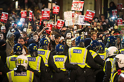 © Licensed to London News Pictures. 05/11/2015. London, UK. Demonstrators clash with riot police during An anti-capitalist  protest organised by the group Anonymous outside Parliament in Westminster on bonfire night 05, November 2015. Bonfire night, also known as Guy Fawkes night, is an annual commemoration of when Guy Fawkes, a member of the Gunpowder Plot, was arrested for attempting to blow up the House of Lords at parliament.   Photo credit: Ben Cawthra/LNP
