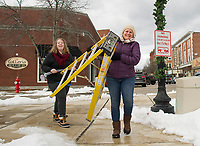 Skylor Beery and Linda Heney work their way down Main Street decorating for the holidays with Celebrate Laconia on Saturday afternoon.  (Karen Bobotas/for the Laconia Daily Sun)
