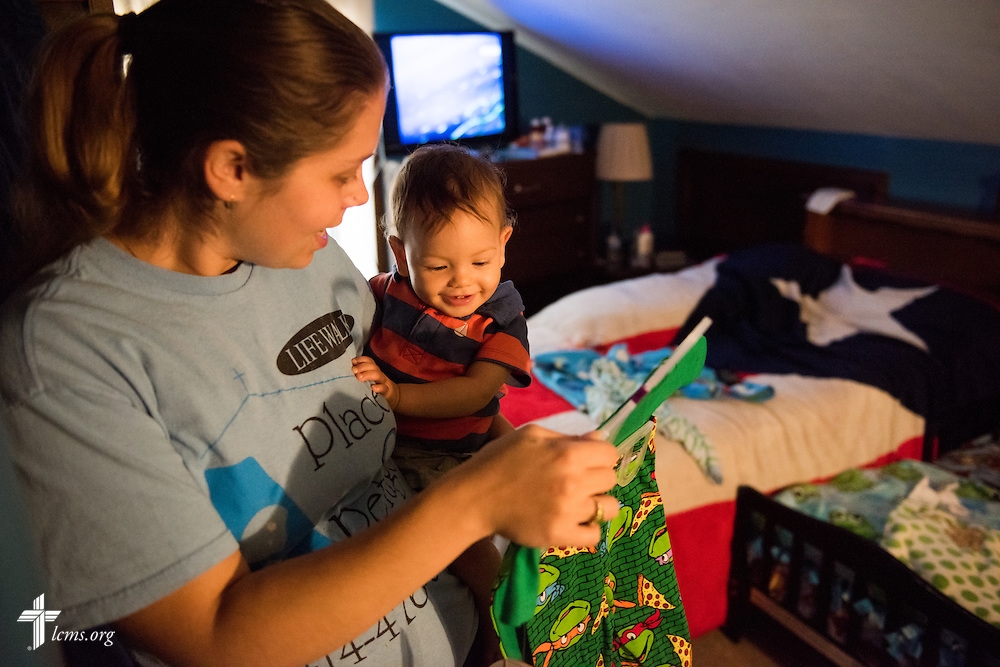 Resident and expectant mother Tiffany Busse options pajamas to her son Ezekiel Vela during bedtime at A Place of Refuge on Tuesday, Sept. 1, 2015, in Milwaukee, Wis. LCMS Communications/Erik M. Lunsford
