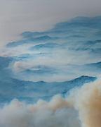 A plane is dwarfed by the smoke plumes as it flies north. ©2016 Sivani Babu