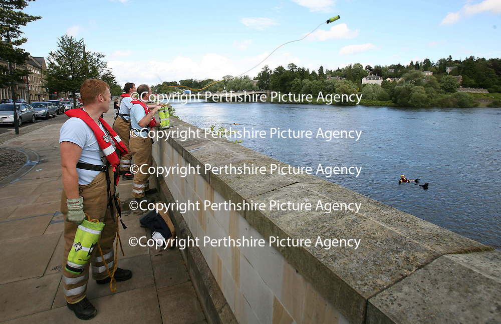 Tayside Fire & Rescue firefighters training with new river rescue equipment on the River Tay in Perth. 14.08.07<br /> A firefighter throws a lifeline to a collegue who is acting as a casualty in the River.<br /> Picture by Graeme Hart.<br /> Copyright Perthshire Picture Agency<br /> Tel: 01738 623350  Mobile: 07990 594431