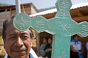 "25 APRIL 2005 - SAN CRISTOBAL DE LAS CASAS, CHIAPAS, MEXICO: A Mayan Indian man carries a cross into a church in the Chamulan Indian community of Yaaltsunum near San Cristobal de las Casas. The Catholic Church in the Chiapas highlands is facing a threat from evangelical Protestant churches, which are experiencing explosive growth, and from ""traditionalist"" Catholic churches, which are not affiliated with the San Cristobal diocese and are controlled by local politicians and powerful indigenous leaders affiliated with the politicians. The traditionalists burn down churches and chapels affiliated with the diocese, threaten the priests and put indigenous men who worship with the diocese in jail.  PHOTO BY JACK KURTZ"