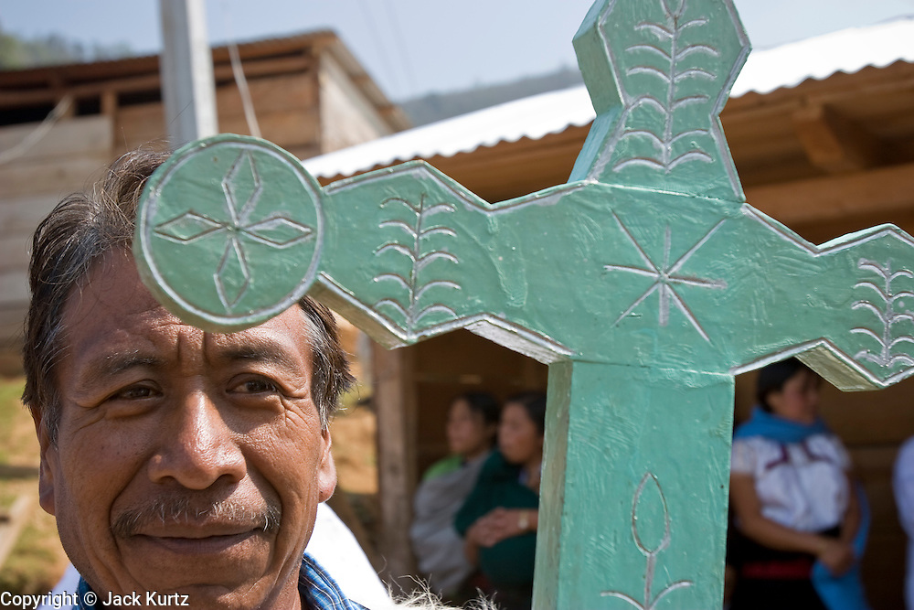 """25 APRIL 2005 - SAN CRISTOBAL DE LAS CASAS, CHIAPAS, MEXICO: A Mayan Indian man carries a cross into a church in the Chamulan Indian community of Yaaltsunum near San Cristobal de las Casas. The Catholic Church in the Chiapas highlands is facing a threat from evangelical Protestant churches, which are experiencing explosive growth, and from """"traditionalist"""" Catholic churches, which are not affiliated with the San Cristobal diocese and are controlled by local politicians and powerful indigenous leaders affiliated with the politicians. The traditionalists burn down churches and chapels affiliated with the diocese, threaten the priests and put indigenous men who worship with the diocese in jail.  PHOTO BY JACK KURTZ"""