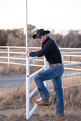cowboy leaning on a fence at dusk