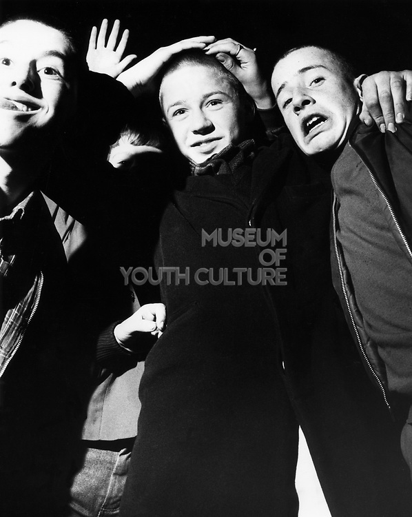 A group of three skinhead boys, at a club, posing for the camera, UK, 1980's.