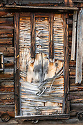 Decaying wood strip pattern on a cabin window shutter. Chicken, Alaska, USA. Chicken is one of the few surviving gold rush towns in Alaska. Mining and tourism keep it alive in the summer, and about 17 people stay through the winter. Gold miners settling here in the late 1800s wanted to name it after the local ptarmigan birds, but couldn't agree on the spelling, so instead called it Chicken to avoid embarrassment. A portion of Chicken including early 1900s buildings and the F.E. Company Dredge No. 4 (Pedro Dredge) is listed as the Chicken Historic District on the National Register of Historical Places. Chicken can be reached via Chicken Airport or Alaska Route 5, the Taylor Highway, which is not maintained from mid-October through mid-March.