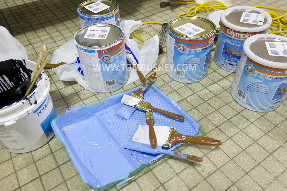 Middletown, New York - Paint and paint brushes by the pool at the Middletown YMCA that was recently emptied and then repainted. The pool and other areas of the YMCA are briefly closed each year for maintenance.