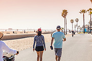 Couple Walking On The Huntington Beach Boardwalk With Pier In Background