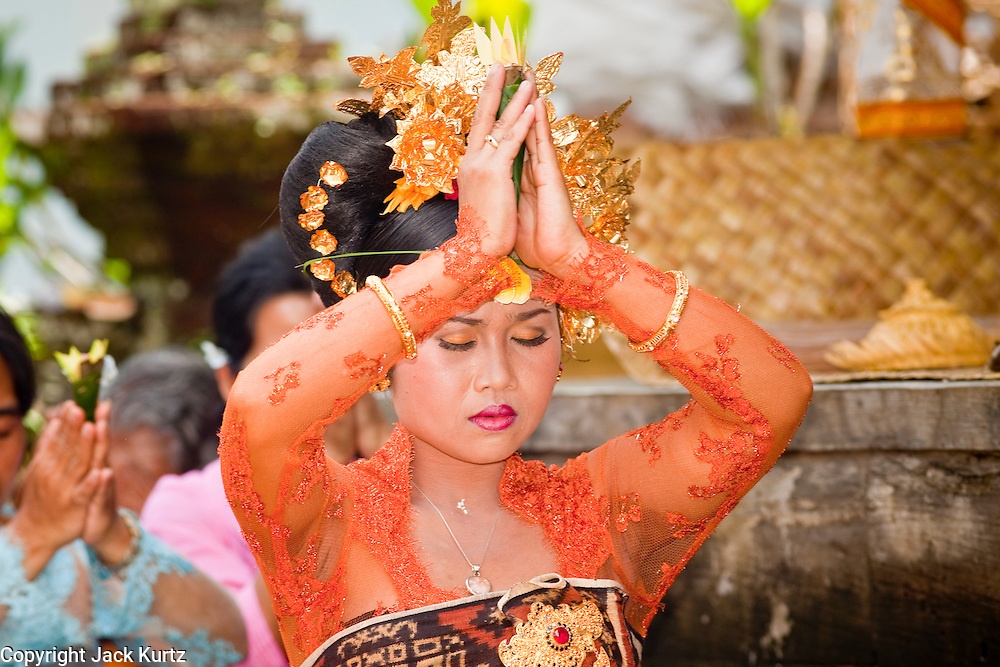 Apr. 22 - UBUD, BALI, INDONESIA:   The bride prays during a wedding in a home in Ubud, Bali, Indonesia. Weddings in Bali have three parts, the first is the ceremony where the couple is wedded. Then the wedding party goes to the bride's family home so the bride can say goodbye to her family. Then there is a wedding reception which is quite similar to western wedding receptions.  Photo by Jack Kurtz/ZUMA Press.