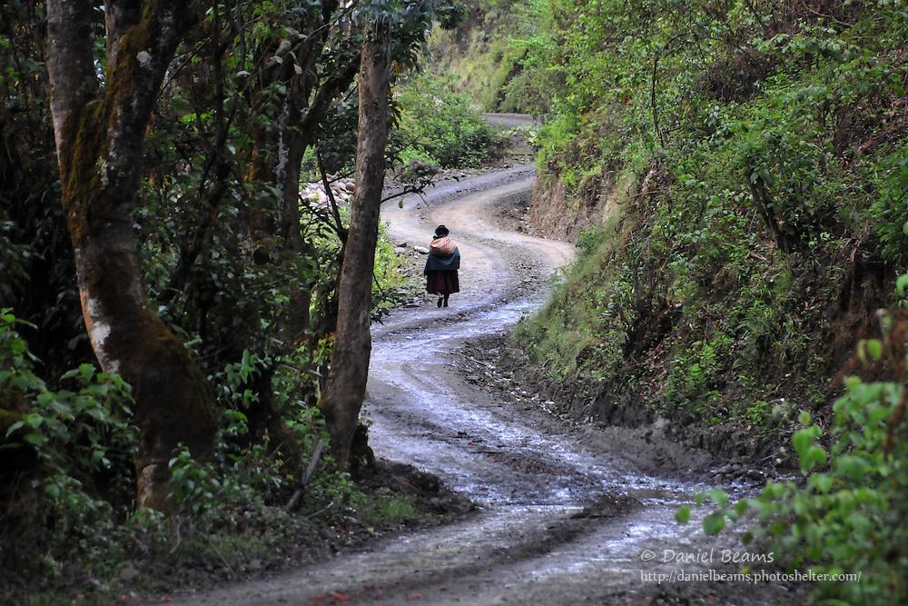 Woman walking on winding road near Sorata, Bolivia