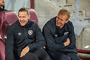 Peter Haring (#5) of Heart of Midlothian FC (left) and Zdenek Zlamal (#1) of Heart of Midlothian FC share a joke as they sit in the technical area before the Betfred Scottish Football League Cup quarter final match between Heart of Midlothian FC and Aberdeen FC at Tynecastle Stadium, Edinburgh, Scotland on 25 September 2019.