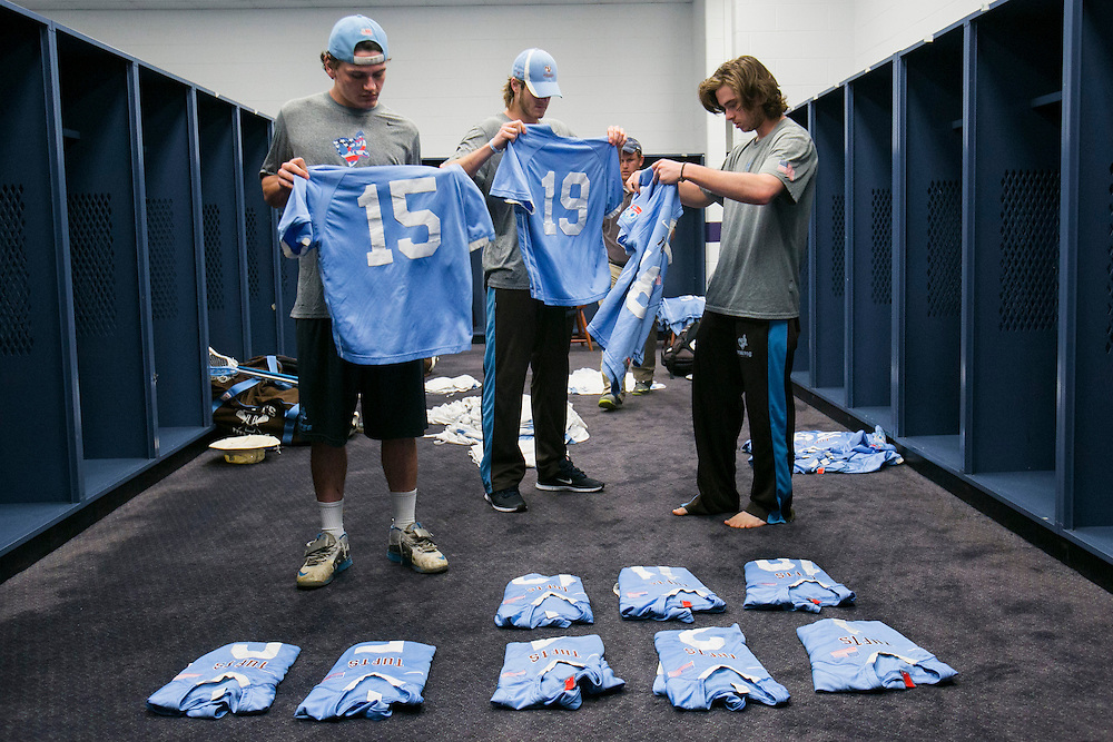 05/25/2014 - Baltimore, Md. - From left, Nate Marchand, A14, Beau Wood, E14, and Austin Carbone, A17, lay out the uniforms for their teammates in the locker room before the NCAA Division III Men's Lacrosse National Championship game at M&T Bank Stadium on May 25, 2014. (Kelvin Ma/Tufts University)