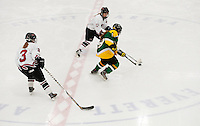 Concord's Sorrell Bourgeois (3) and Annie Mullen (27) and Bishop Guertin's Brianna Bermingham during varsity hockey at Everett Arena Saturday afternoon.  (Karen Bobotas/for the Concord Monitor)