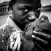 Village of Kerouane in Guinea konakry on the road to Kankan, boy with two pigeons in his hands.
