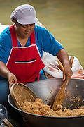 "17 NOVEMBER 2012 - BANGKOK, THAILAND:  A woman makes ""mee krob"" (Thai fried noodles with tamarind sauce) at a floating market in the Thonburi section of Bangkok. Floating markets are common in parts of Thailand with lots of canals. Bangkok used to be known as the ""Venice of the East"" because of the number of waterways the criss crossed the city. Now most of the waterways have been filled in but boats and ships still play an important role in daily life in Bangkok. Thousands of people commute to work daily on the Chao Phraya Express Boats and fast boats that ply Khlong Saen Saeb or use boats to get around on the canals on the Thonburi side of the river. Boats are used to haul commodities through the city to deep water ports for export.    PHOTO BY JACK KURTZ"