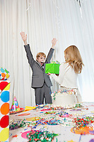 Sister giving gift to surprised birthday boy with arms raised.