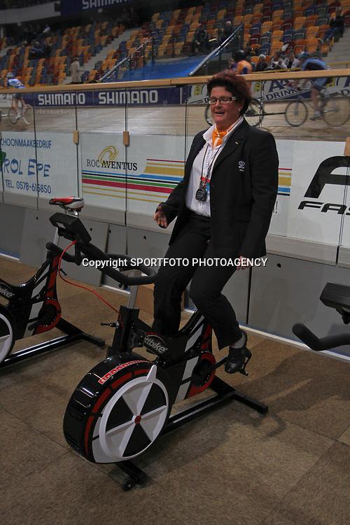 Jurylid zelf aan het fietsen op het NK Baan