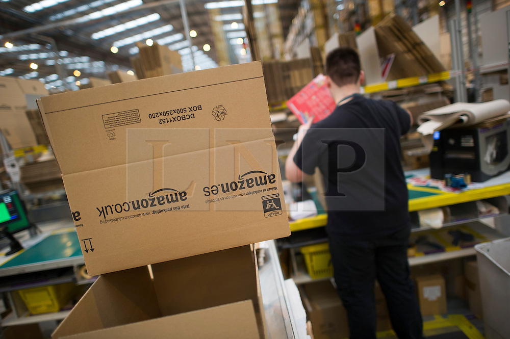 © London News Pictures. 28/11/2013. Peterborough, UK. Boxes being packed. Staff at the Amazon Peterborough fulfilment centre process orders as they prepare for 'Cyber Monday', busiest online shopping day of the year. On Cyber Monday 2012, Amazon.co.uk saw more than 3.5 million items ordered on the site, at a rate of around 41 items per second. Over 15000 extra staff are drafted in to Amazon nation wide over the festive period to cope with the extra demand with over 1000 extra staff being deployed at the Peterborough site. Photo credit: Ben Cawthra