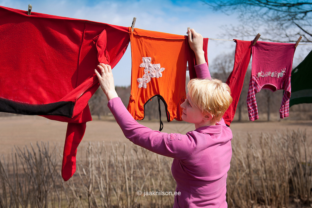 Caucasian  Woman Hanging Up Wet Laundry on Clothes Line