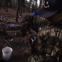 Fearful of being robbed, a matsutake mushroom picker arms himself with a gun in the Willamette National Forest of Oregon. Competition for the matsutake is so fierce that many pickers carry weapons to protect themselves and their valuable mushrooms. Despite the best efforts of local officials, violence has been known to erupt during the harvest. In 1996, The Oregonian reported that five shootings occurred in the Mushroom Camp during the six weeks that it was open.